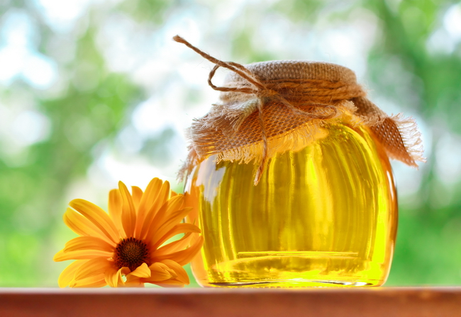 fragrant honey in glass jar with flower